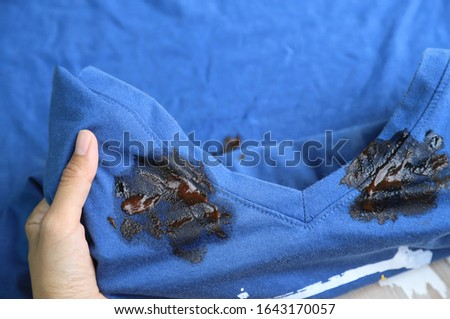 Hand showing dirty stain on collar shirt from accident in eating. dirt stains for cleaning concept  #1643170057