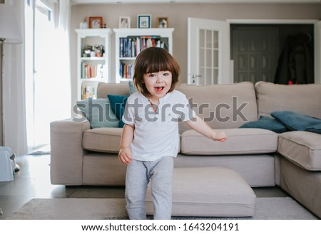 Little active boy having fun running around living room at home. Weekend leisure activity lifestyle.  #1643204191
