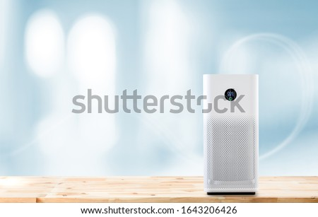 air purifier a living room,  air cleaner removing fine dust in house. protect PM 2.5 dust and air pollution concept Royalty-Free Stock Photo #1643206426