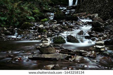 Waterfall in autumnal forest. Long exposure photo. Slow motion water photography. Copy space. Flowing water. Slow shutter speed photography of waterfall and water