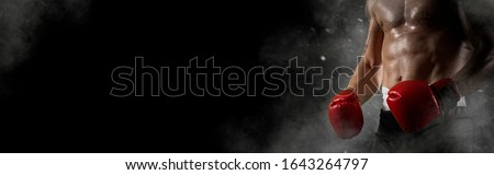 Boxer in red gloves on black background. Sports banner. Horizontal copy space background Royalty-Free Stock Photo #1643264797