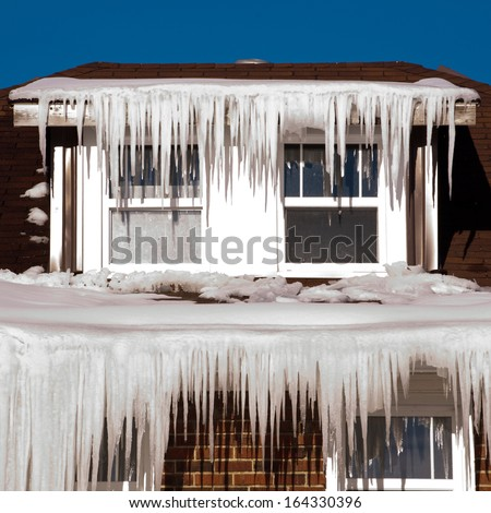 Icicles hanging from a house roof Royalty-Free Stock Photo #164330396