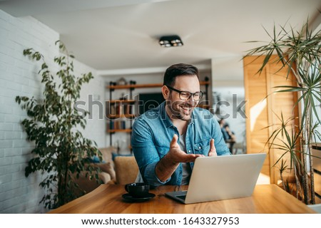 Portrait of a cheerful man having video call on laptop computer. Royalty-Free Stock Photo #1643327953