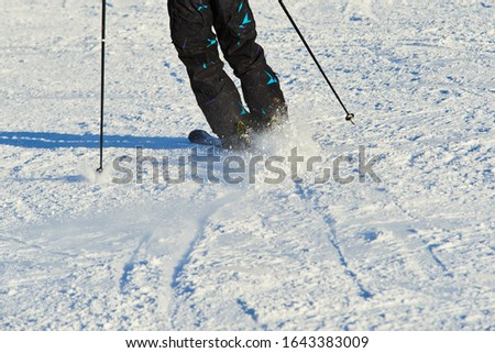 Detail on skis and legs of skier skiing on ski slope #1643383009