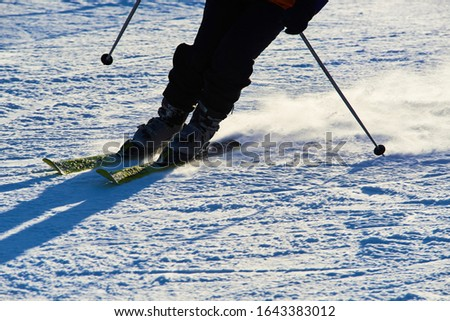 Detail on skis and legs of skier skiing on ski slope #1643383012