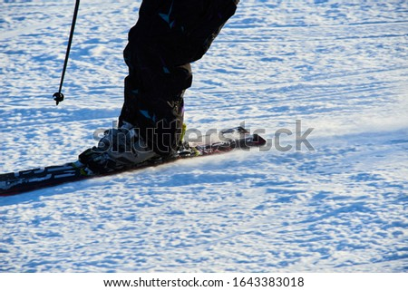 Detail on skis and legs of skier skiing on ski slope #1643383018