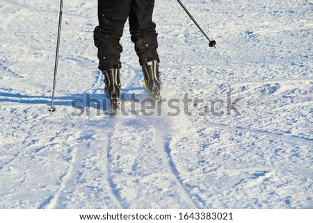 Detail on skis and legs of skier skiing on ski slope #1643383021
