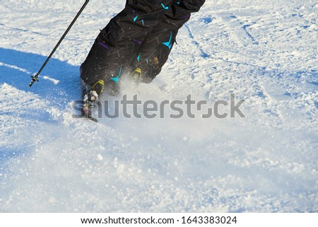 Detail on skis and legs of skier skiing on ski slope #1643383024