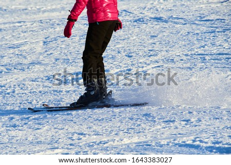 Detail on skis and legs of skier skiing on ski slope #1643383027