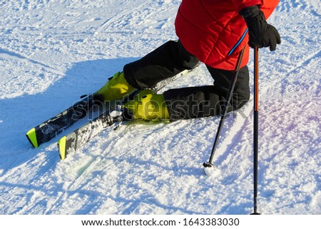 Detail on skis and legs of skier skiing on ski slope #1643383030