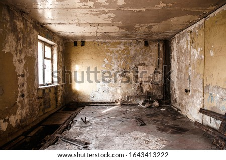 Ruined apartment of deserted hotel, old room with one window and damaged cracked walls, abandoned house, horror style interior, mystical place Royalty-Free Stock Photo #1643413222