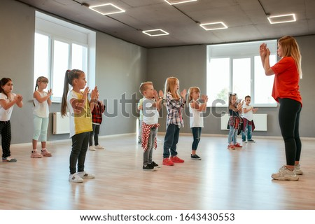 Learning a new dance. Group of little boys and girls dancing while having choreography class in the dance studio. Dance teacher and children. Contemp dance. Hip hop. Kids and sport. Full length #1643430553