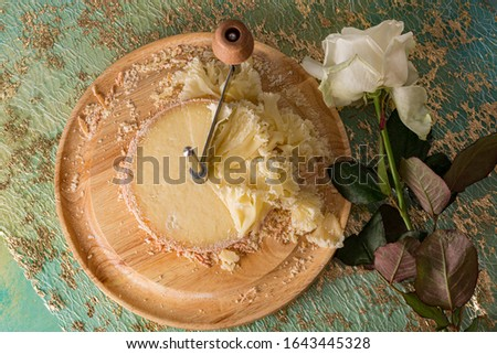 French cheese Monk Head sliced on a wooden round surface. Scraper or knife for slicing and tasting tasty cheese chips on a green table.  White rose flower. Dark background. Shallow depth of field.  #1643445328