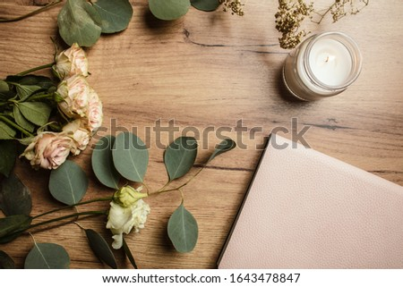 Beautiful flowers with the candle and notebook on the wood background. Holiday card. Holiday background. Planning holiday. #1643478847