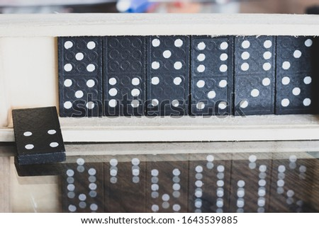 The black Domino Game, made of wood, is placed on a glass-covered wooden table on top. #1643539885