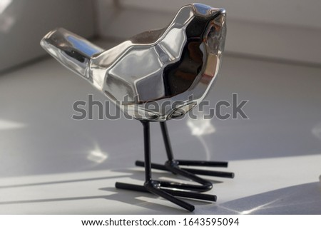 Figures of birds made of metal. Shiny tits in the form of sculptures. Decoration for the interior. Steel birds made in the polygonal style. Figurines in natural light.