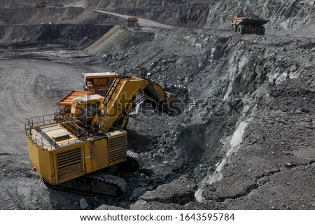 Open pit mining of iron ore and magnetite ores.Loading the iron ore into heavy dump truck at the opencast mining. #1643595784
