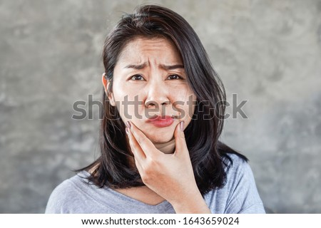 depressed Asian woman having problem with Bell's Palsy/Facial Palsy, hand holding her face  Royalty-Free Stock Photo #1643659024