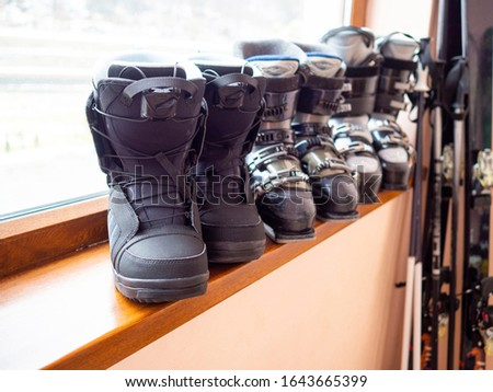 Ski and snowboard boots rental, skis and poles. Skiing equipment rented. Close up. #1643665399