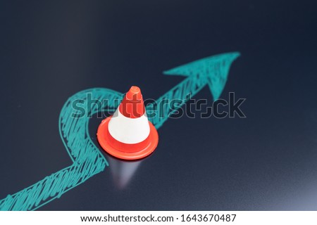 Chalk drawing arrow turn or break through road block traffic pylon on dark blackboard using as obstacle, solution for business problem or break through to success concept. #1643670487