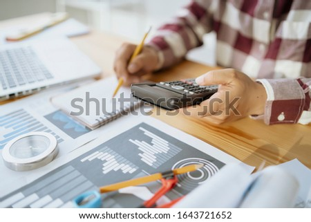 A pensive student man notes in copybook calculate  finance,account concept,Asian business man entrepreneur Startup use calculator calculating financial expense office,online technology   #1643721652