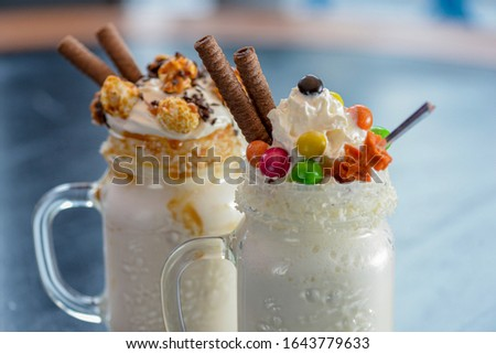 Two glasses or jars of freak shakes on rustic wooden table. Caramel marshmallow candy milk shake cocktail with whipped cream, cookies, waffles and other sweet treats. Sweet dessert drinks. #1643779633