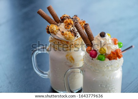 Two glasses or jars of freak shakes on rustic wooden table. Caramel marshmallow candy milk shake cocktail with whipped cream, cookies, waffles and other sweet treats. Sweet dessert drinks. #1643779636