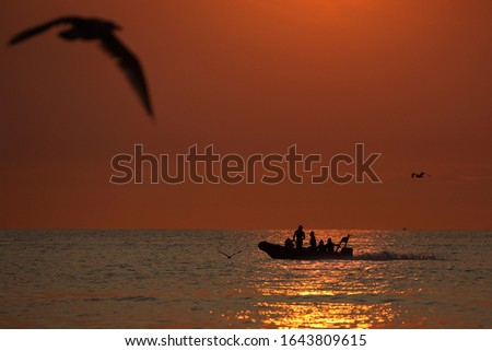 Young people in a small boat on sea are enjoying a warm summer evening #1643809615
