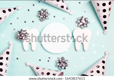 Happy Dentist's Day greeting card with teeth and holiday caps on a blue background. Copy space for text.