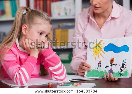 Child psychologist with a sad little girl, the doctor looks at the child's picture
