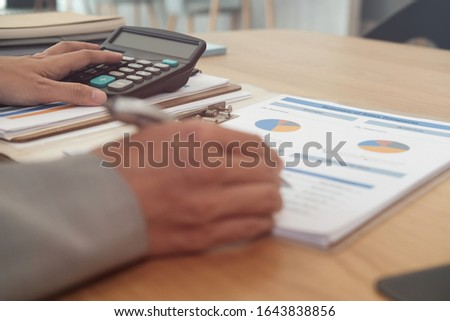financial adviser working with calculator, business document at office. accountant doing accounting & calculating revenue & budget. bookkeeper making calculation. finance & economy concept #1643838856