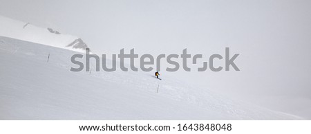 Skier downhill on snowy off-piste ski slope and mountains in fog at gray winter day before blizzard. Georgia, region Gudauri, Caucasus Mountains. Panoramic view. #1643848048