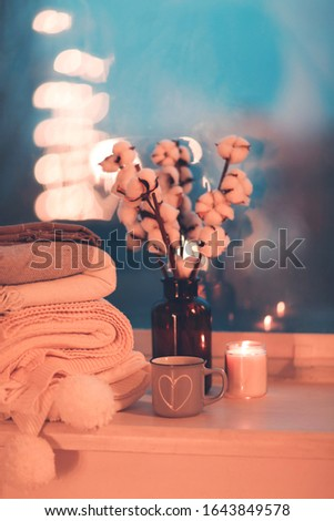Stack of knitted plaids with gray mug and burning candle on cozy window #1643849578