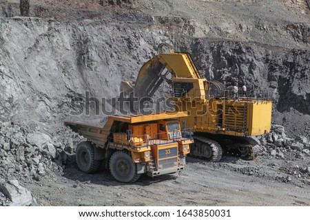 Open pit mining of iron ore and magnetite ores.Loading the iron ore into heavy dump truck at the opencast mining. #1643850031