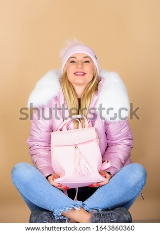 Total pastel outfit. Tender combination. Matching accessories. Fashion accessory. Girl adorable model showing her fancy leather backpack. Backpack is all you need. Little backpack and knitted hat. #1643860360
