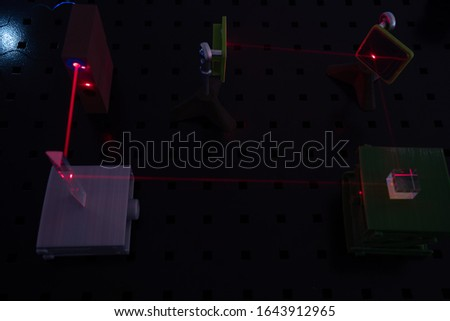 Experiment in optic lab with laser device. Red laser on optical table in physics laboratory #1643912965