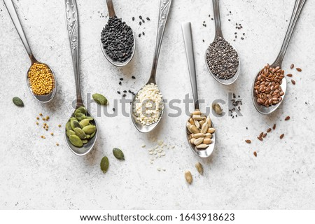 Various Seeds Assortment on white background. Set of  sesame seeds, flax seed, sunflower seeds, pumpkin seed, chia, hemp seeds in spoons, healthy food ingredients, top view, copy space. #1643918623
