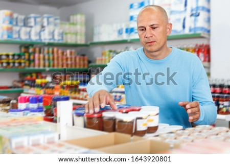 Portrait of concentrated man making purchases in the grocery department of the supermarket #1643920801
