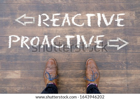 """Man looking down at the words """"REACTIVE"""" and """"PROACTIVE"""" written on the floor #1643946202"""