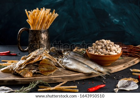 Salty dried fish roach and yellow stripe scad fish with dried fish sticks and pistachios on wooden board on black table background.