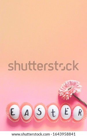 Vertical easter image with negative space. Bright Easter image with fresh spring flower on the pink background. White eggs with text - Easter on the bright colorful background.