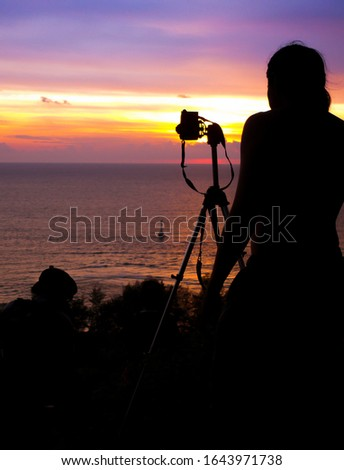 Silhouette of a man standing on a mountain to take a picture of the sunset