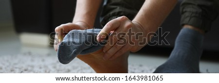 Man at home in morning puts gray socks on his leg. For a long time do not change clothes concept #1643981065