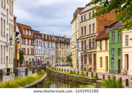 On the streets of Wismar old town. Colorful houses along the canal of Grube river, Wismar city, Mecklenburg-Vorpommern state, Germany Royalty-Free Stock Photo #1643992588