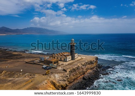 Reflexes on the water puddles of cliffs and lighthouse, Jandia tip in coast of Fuerteventura, Canary islands. Aerial drone shot, october 2019
