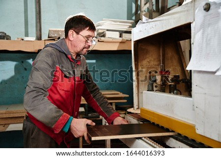 Process of production and manufacture of wooden furniture in furniture factory. Worker carpenter man in overalls processes wood on special equipment #1644016393
