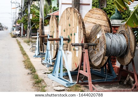 Empty wooden telecommunication cable drum or coil on walking street #1644020788
