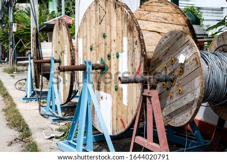 Empty wooden telecommunication cable drum or coil on walking street #1644020791