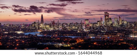 Wide panoramic view of the illuminated skyline of London, United Kingdom, after a sunset with orange and pink colors