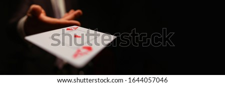 Businessman in suit throws his hand playing card ace of worms to opponent on a black background. Winning in business payout concept Royalty-Free Stock Photo #1644057046